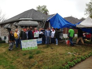 The crew of volunteers pose with the homeowner (in the middle holding sign) for a photo during National Rebuilding Day in St. Louis, Mo.